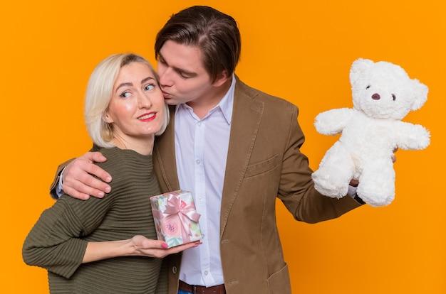 Glücklicher mann des jungen schönen paares mit teddybär, der seine reizende überraschte freundin mit geschenk in händen küsst, die in der liebe glücklich zusammen sind