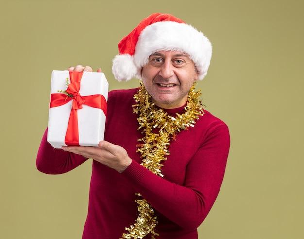 Glücklicher mann des mittleren alters, der weihnachtsweihnachtsmütze mit lametta um den hals hält, der weihnachtsgeschenk hält, das kamera mit lächeln auf gesicht steht, das über grünem hintergrund steht