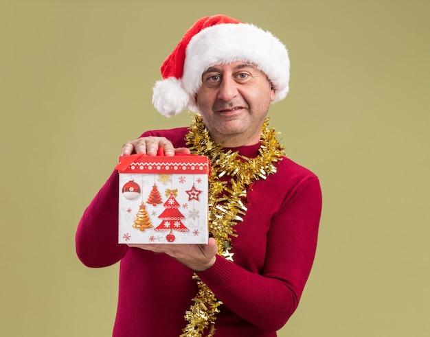 Glücklicher mann des mittleren alters, der weihnachtsweihnachtsmütze mit lametta um den hals hält, der weihnachtsgeschenk hält, das kamera schaut, die fröhlich über grünem hintergrund steht