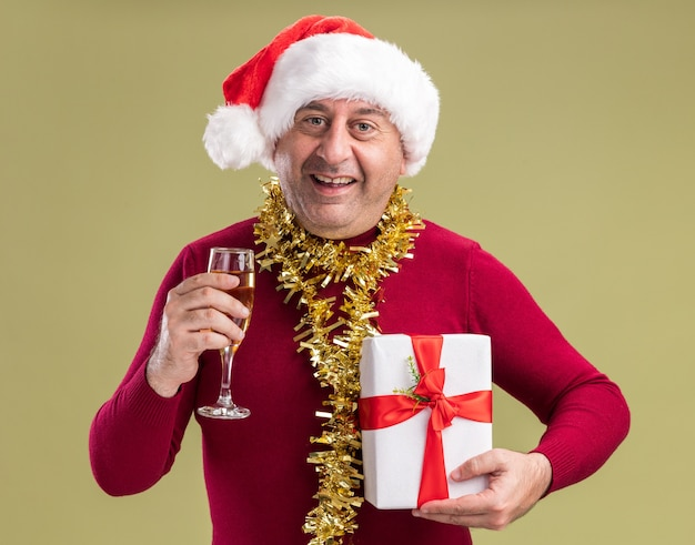 Glücklicher mann des mittleren alters, der weihnachtsweihnachtsmütze mit lametta um den hals hält, der weihnachtsgeschenk und glas champagner betrachtet kamera mit lächeln auf gesicht steht über grünem hintergrund