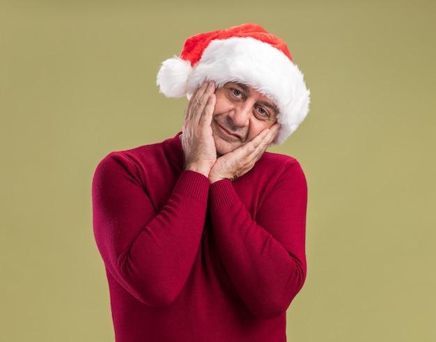Glücklicher mann des mittleren alters, der weihnachtsweihnachtsmütze trägt und kamera mit lächeln auf gesicht steht, das über grünem hintergrund steht