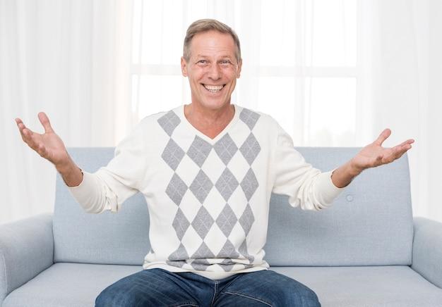 Glücklicher mann des mittleren schusses, der auf der couch sitzt