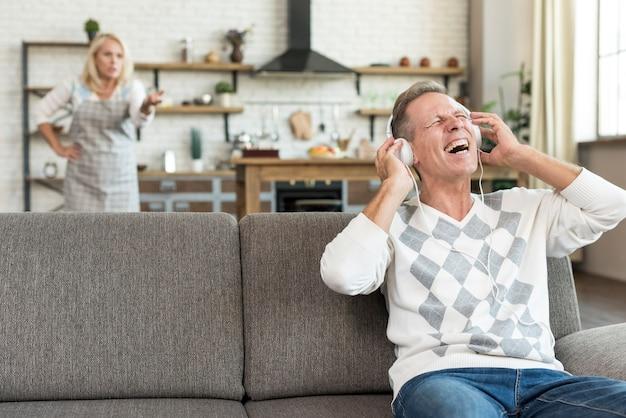 Glücklicher mann des mittleren schusses mit kopfhörern auf der couch