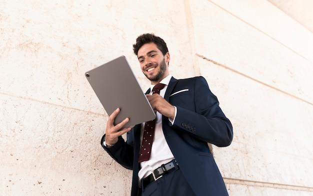 Glücklicher mann des niedrigen winkels, der an tablette arbeitet