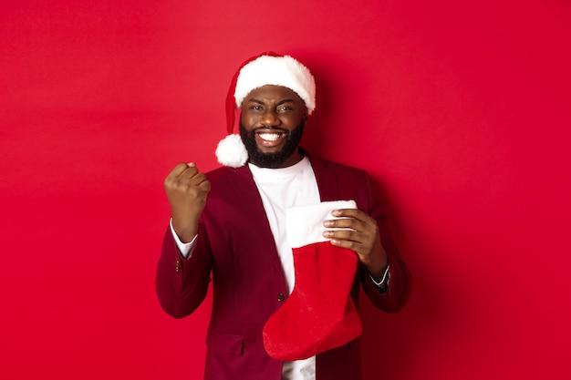 Glücklicher mann freut sich, erhält geschenke in weihnachtssocke, macht faustpumpe und lächelt zufrieden, steht auf rotem hintergrund.