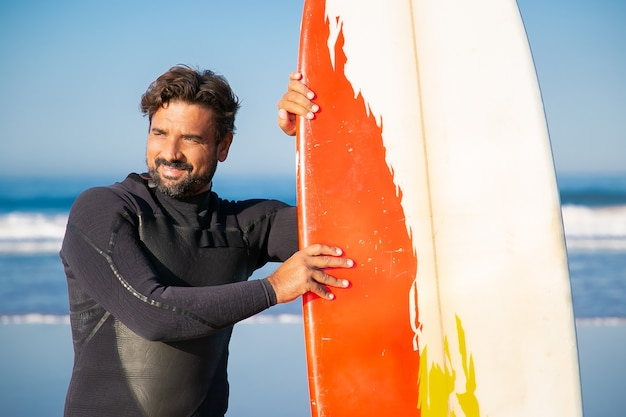 Glücklicher mann im badeanzug, der mit surfbrett steht und wegschaut. kaukasischer bärtiger surfer, der sich an bord lehnt und lächelt