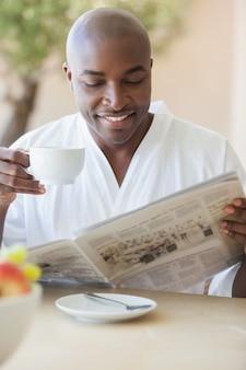 Glücklicher mann im bademantel, der kaffee auf terrasse trinkt