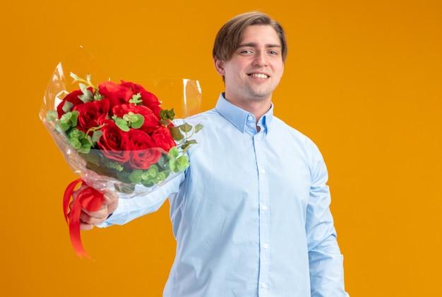 Glücklicher mann im blueshirt, der strauß der roten rosen hält, die kamera betrachten, die fröhlich valentinstagkonzept steht, das über orange wand steht