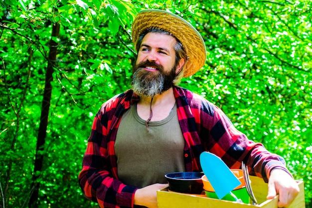 Glücklicher mann im frühlingsgarten. gärtner in öko-bauernhof mit gartenwerkzeugpflanzung.