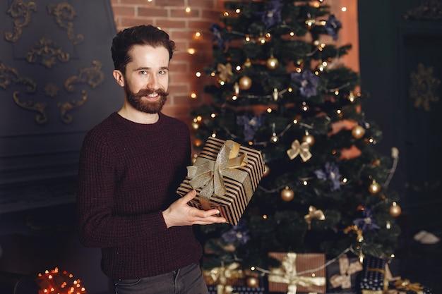Glücklicher mann im roten pullover. mann vor dem kamin. männchen auf dem hintergrund des weihnachtsbaumes.