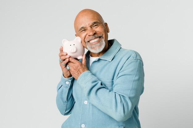 Glücklicher mann im ruhestand, der sein sparschwein hält holding