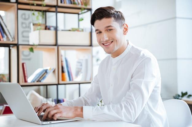 Glücklicher mann im weißen hemd mit laptop-computer beim betrachten der kamera. coworking.