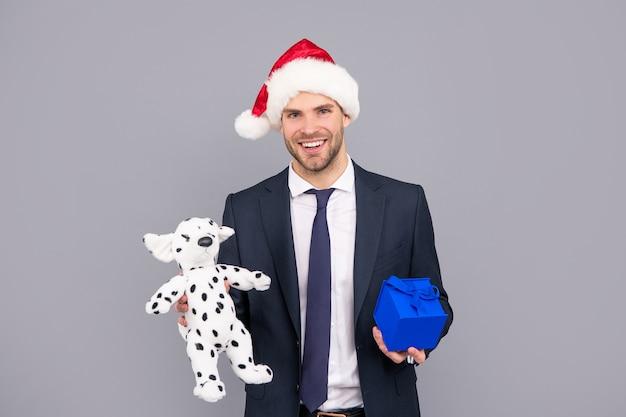 Glücklicher mann in business-anzug und weihnachtsmann-hut halten geschenkbox und spielzeug, abschluss.