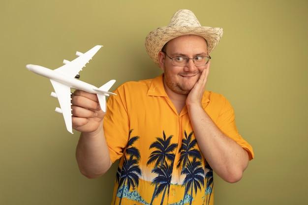 Glücklicher mann in den gläsern, die orangefarbenes hemd im sommerhut halten, der spielzeugflugzeug hält, das es betrachtete, staunte, über grüner wand stehend
