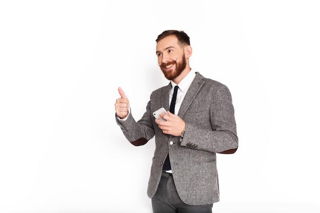 Glücklicher mann in der grauen klage zeigt den daumen, der smartphone in seinem arm hochhält