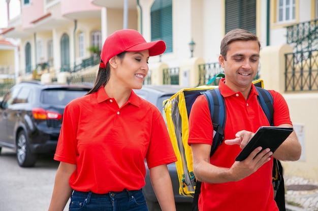 Glücklicher mann in der roten kappe, die adresse zum kollegen zeigt. lächelnde kuriere arbeiten zusammen und liefern bestellungen zu fuß.