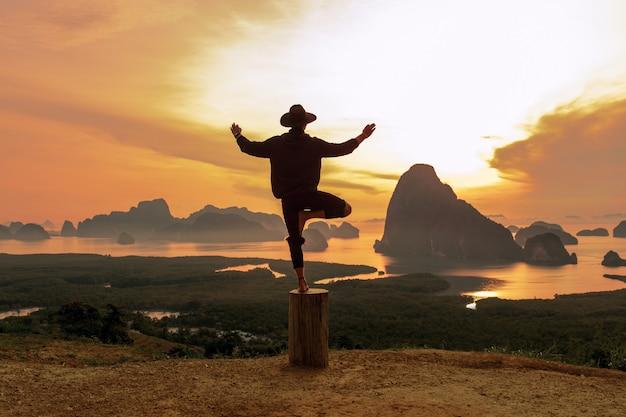 Glücklicher mann in der schwarzen kleidung, welche die yogahaltung steht auf dem baum tut