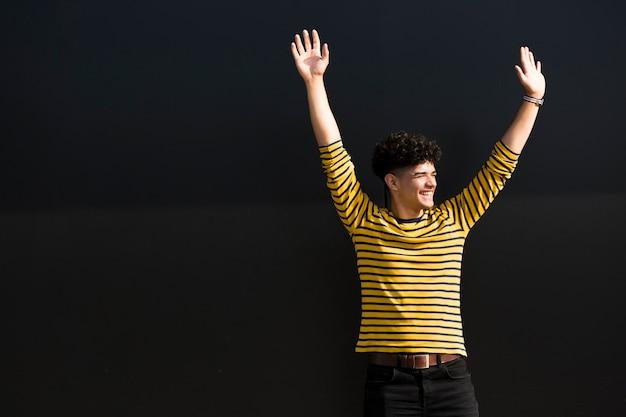 Glücklicher mann in gestreiftem hemd mit den händen oben im studio