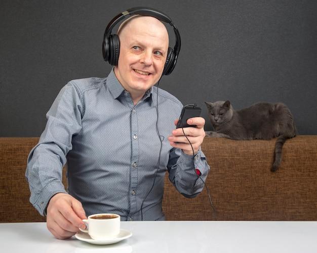 Glücklicher mann in tragbaren kopfhörern in voller größe hört musik mit einem digitalen player.