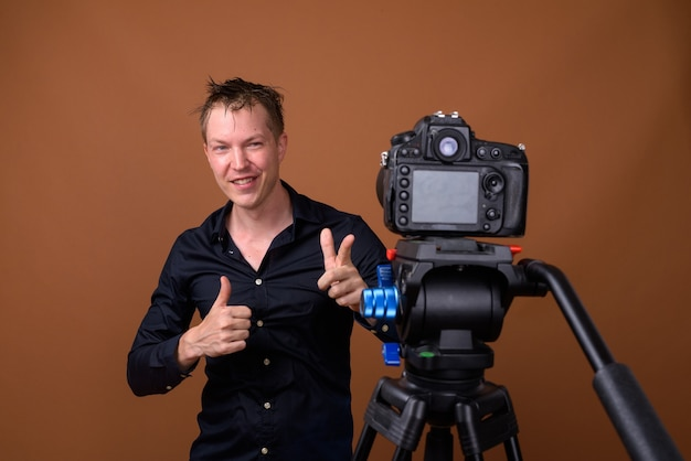 Glücklicher mann influencer vlogging mit dslr-kamera