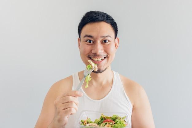 Glücklicher mann isst gesunde salatmahlzeit.