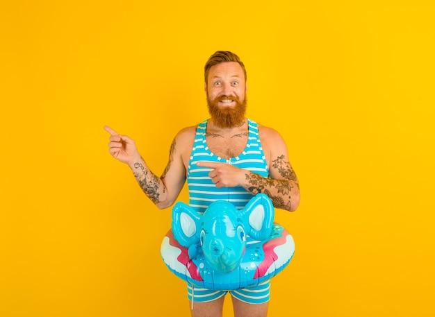 Glücklicher mann mit aufblasbarem donut mit elefant ist bereit zu schwimmen