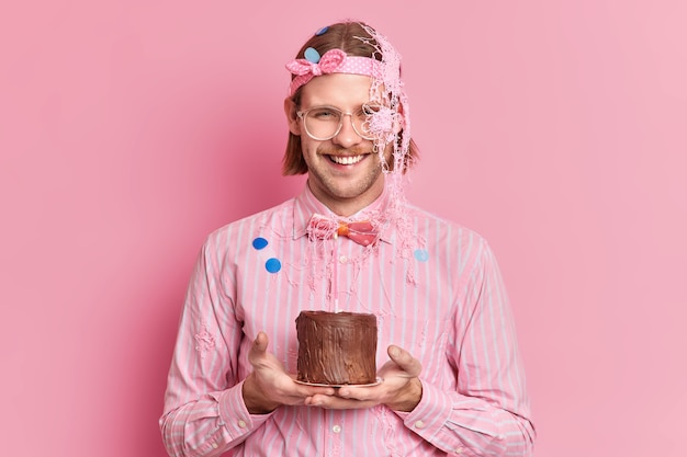Glücklicher mann mit borsten fröhlichen ausdruck hält kuchen mit kerze, um freund mit jubiläum zu gratulieren trägt festliches outfit große brille lächelt positiv isoliert gegen rosa wand