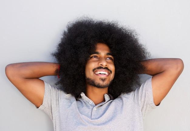 Glücklicher mann mit dem afro, das entspannt mit den händen im haar schaut