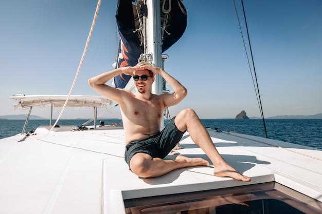 Glücklicher mann mit einem niedlichen lächeln, shorts und sonnenbrille tragend, sitzend und die sonne mit seiner hand bedeckend, auf seiner weißen teuren yacht.