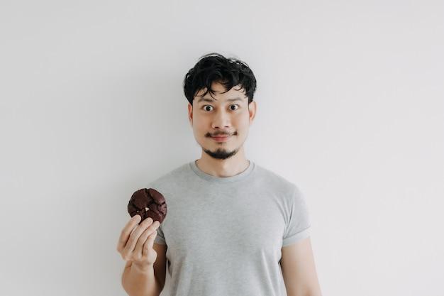Glücklicher mann mit einem schokoladenkeks isoliert auf weißem hintergrund