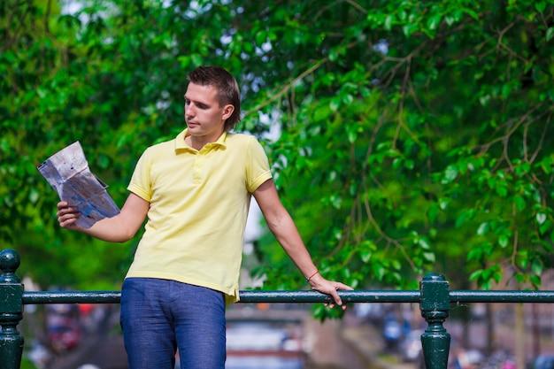Glücklicher mann mit einem stadtplan und einem rucksack in europa