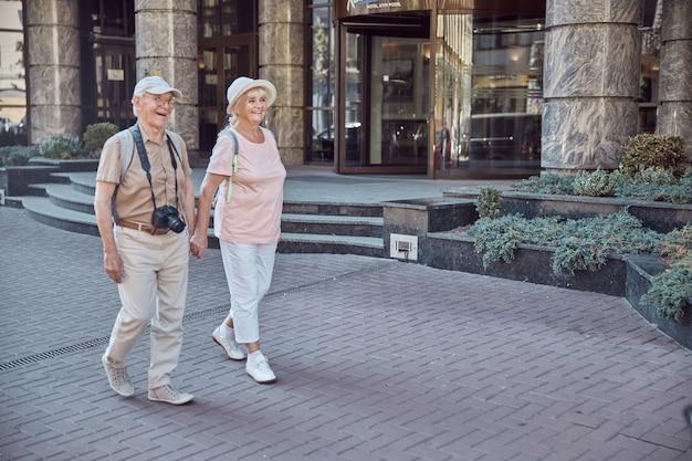Glücklicher mann mit einer digitalkamera und einer stilvollen älteren dame, die hand in hand geht