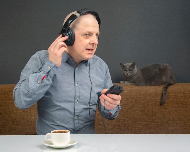 Glücklicher mann mit einer tasse kaffee in tragbaren kopfhörern hört musik unter verwendung eines spielers.
