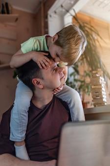 Glücklicher mann mit freudigen kindern, die laptop und kopfhörer während seiner arbeit zu hause beim sitzen auf sofa zu hause, home office mit zusammen mit kindern, leben während der quarantäne verwenden