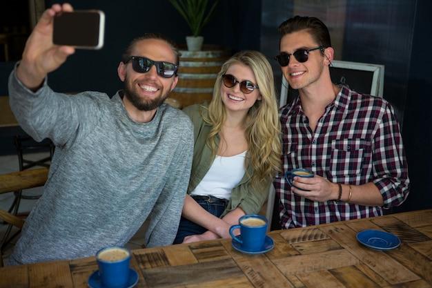 Glücklicher mann mit freunden, die selfie am tisch im kaffeehaus nehmen