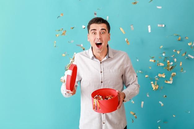 Glücklicher mann mit geschenk und fallendem konfetti