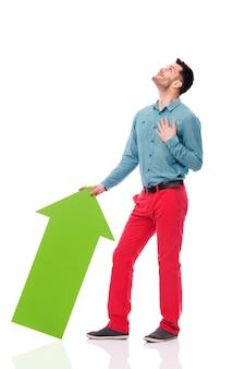 Glücklicher mann mit grünem pfeil, der nach oben schaut