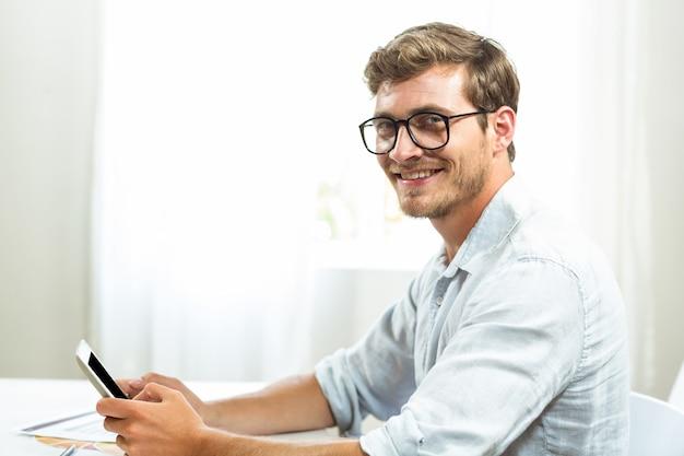 Glücklicher mann mit handy im büro