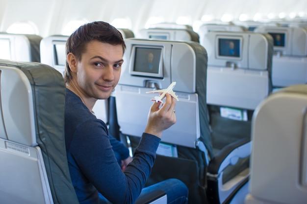 Glücklicher mann mit kleinem flugzeugmodell innerhalb eines großen flugzeugs