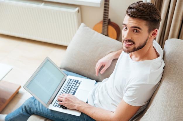 Glücklicher mann mit laptop-computer auf dem sofa zu hause sofa