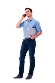 Glücklicher mann mit laptop, der auf dem handy spricht