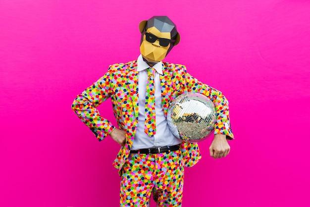 Glücklicher mann mit lustiger niedriger polymaske auf farbiger wand