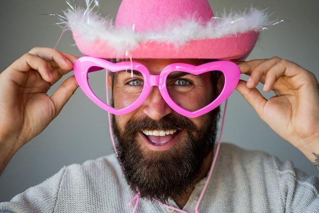 Glücklicher mann mit lustiger rosa brille. hübscher lächelnder junger kerl. positive menschliche mimik und emotionen. lustiger cowboy.