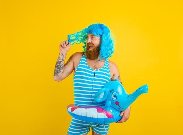 Glücklicher mann mit rettungsring-badeanzug und blauer perücke verhält sich wie eine glückliche frau