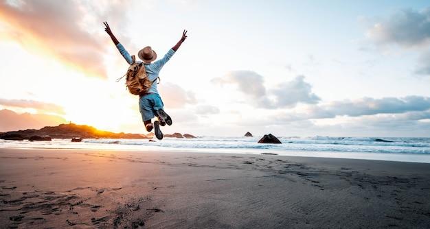 Glücklicher mann mit rucksack, der bei sonnenuntergang über den strand springt