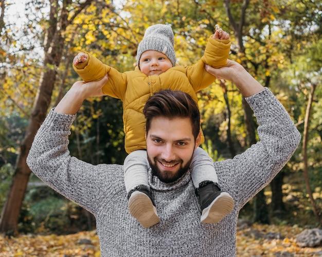 Glücklicher mann mit seinem kind draußen