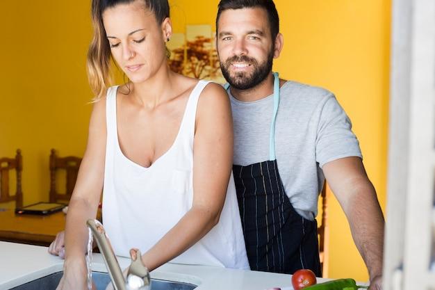 Glücklicher mann mit seiner frau, die in der küche steht