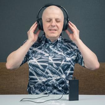 Glücklicher mann mit tragbaren kopfhörern hört musik mit einem player
