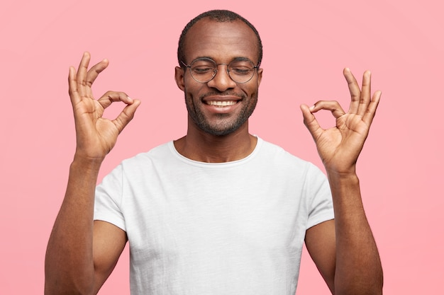Glücklicher mann mittleren alters mit breitem zahnigem lächeln, zeigt ok geste, schließt vor vergnügen die augen, lässig gekleidet, isoliert auf rosa wand