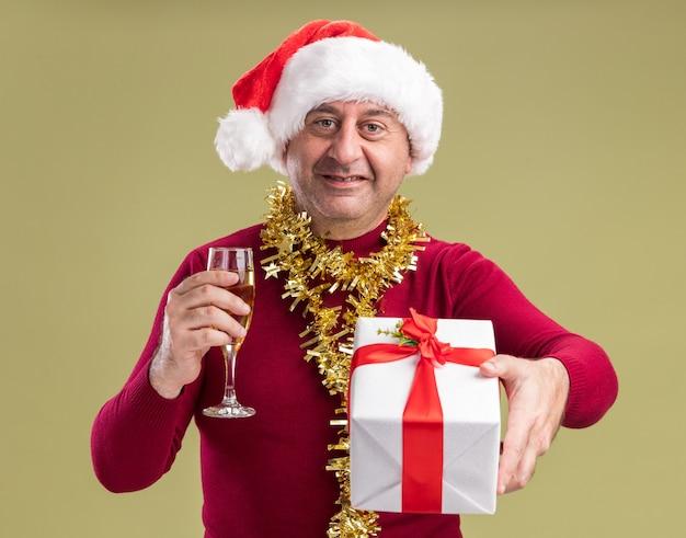 Glücklicher mann mittleren alters mit weihnachtsmütze mit lametta um den hals, der ein weihnachtsgeschenk und ein glas champagner hält und fröhlich über grüner wand steht?